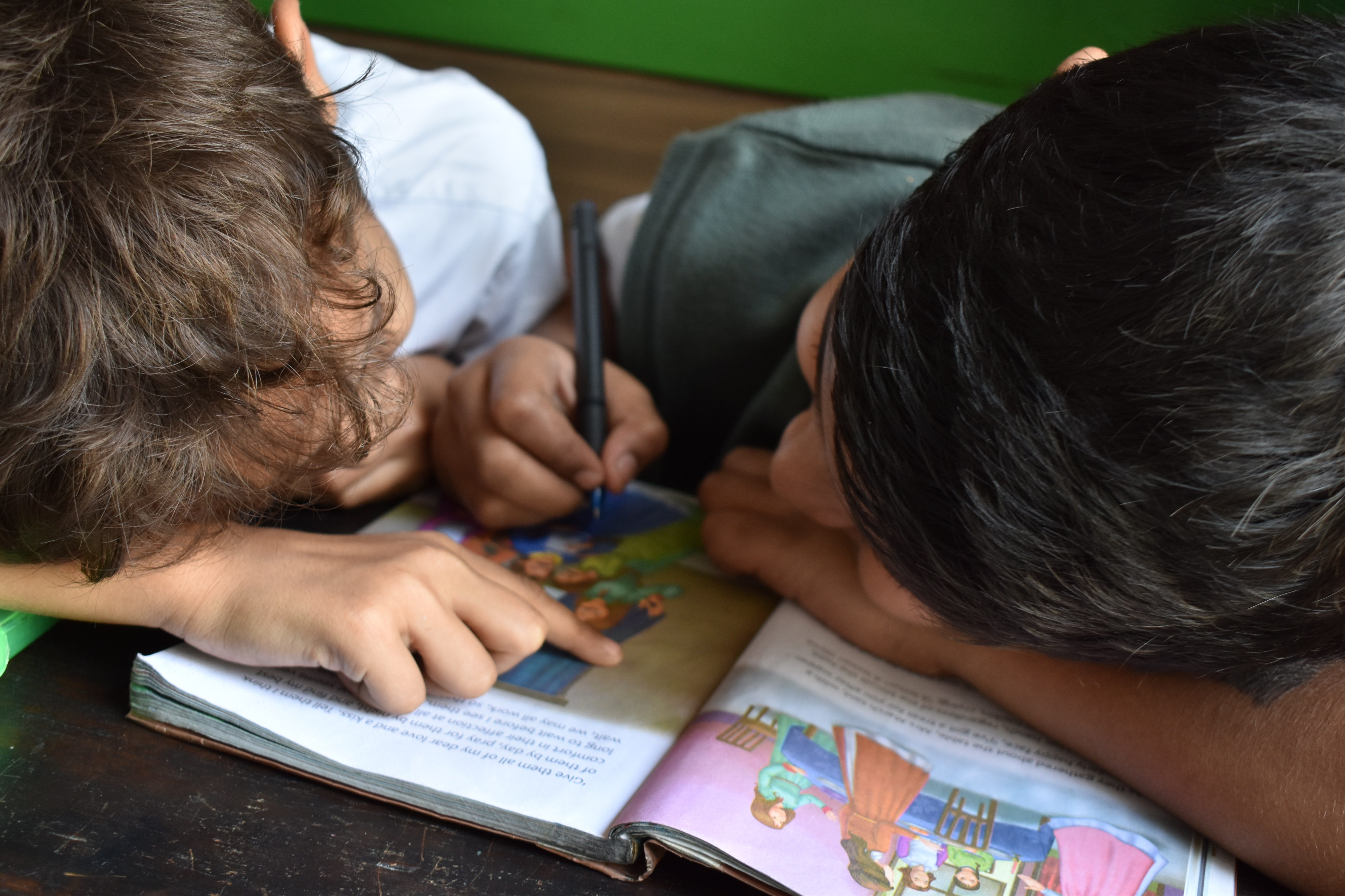Two young children reading a book in school drdp summary of findings sample