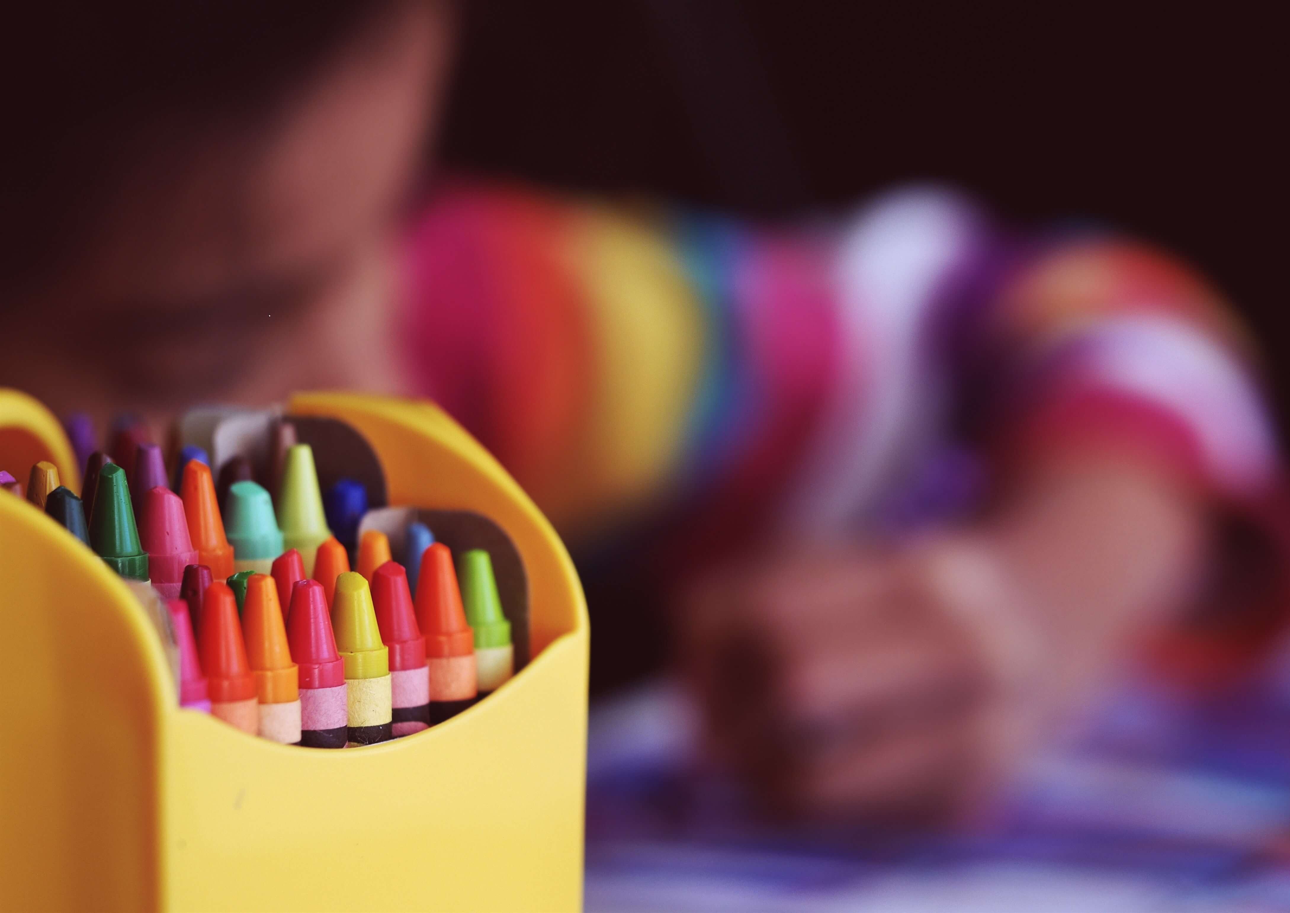 A pack of crayons and a child coloring continuous quality improvement learning genie